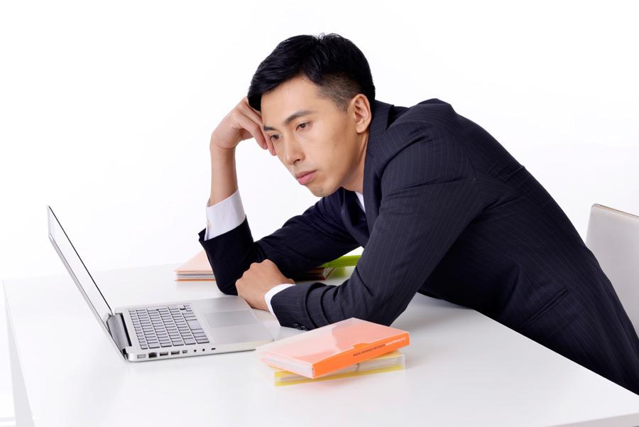パソコンの処理待ちしている男性